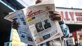 A man reads the Ethiopian newspaper 'The Reporter', depicting the portraits of killed Ambachew Mekon