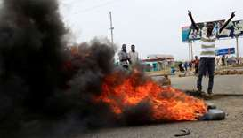 A Sudanese protester gestures near burning tyres used to erect a barricade on a street, demanding th