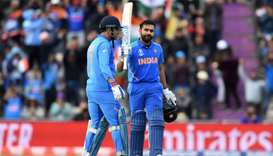 India's Rohit Sharma (R) celebrates with India's Mahendra Singh Dhoni on reaching his century during