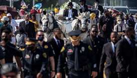 A row of police officers walk ahead of the horse-drawn carriage coffin of George Floyd, whose death