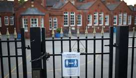A social distancing sign is seen on the gate of a school as the spread of the coronavirus disease (C