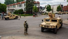 Minnesota National Guard soldiers patrol a street in Minneapolis, Minnesota, as protesters demand ju