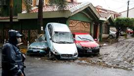 A police officer stands near cars damaged by floods caused by Tropical Storm Amanda, at the San Fran