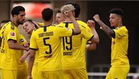 Dortmund's English midfielder Jadon Sancho (right) is congratulated by his teammates after scoring h