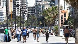 Residents of the Lebanese capital Beirut stroll along the seaside corniche, despite the lingering th