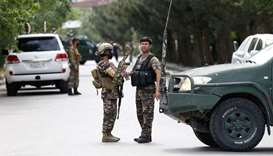 Afghan security forces stand guard near the site of an attack in Kabul, Afghanistan