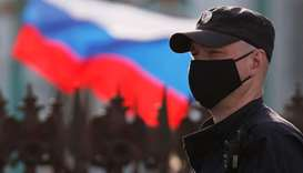A police officer wearing a protective face mask stands guard at Dvortsovaya Square, amid the outbrea