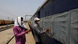 Workers fix mosquito nets on a parked passenger train that will be equipped for the care of coronavi