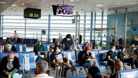 Passengers wearing protective face masks wait for a flight to Nantes at Lisbon's airport in Lisbon,