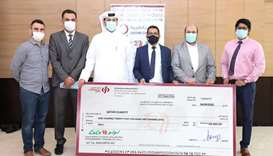 Officials of Qatar Charity and LuLu Hypermarket Qatar at the cheque-handing over ceremony.