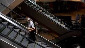A elderly man wearing a protective mask carries a take-away bag as he rides an escalator inside a sh