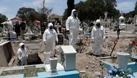 Cemetery workers wearing protective suits complete the burial of a man, who died of the coronavirus