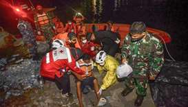 Rescue team members evacuate one of six survivors of a capsized passenger boat carrying 16 people in