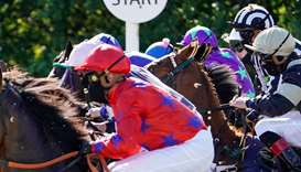 Jockeys ride the horses out of the starting stalls at Newcastle Racecourse in United Kingdom yesterd