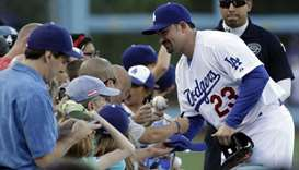 Los Angeles Dodgers' Adrian Gonzalez signs baseball for fans before a game on August 25, 2012. (TNS)