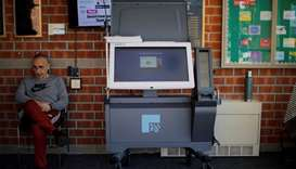 Elections official Bernie O'Hare waits to help voters use a new Election Systems & Software ExpressV