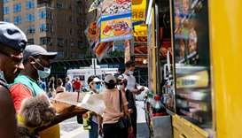 People wearing protective face masks get food from a street vendor near Central Park, in the Manhatt