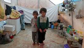 Jumana and Farhan al-Alyawi, a 8-year-old displaced Syrian twins from east Idlib, pose for a picture