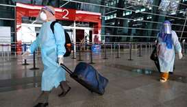 Travellers wearing PPE walk through the Indira Gandhi International Airport in New Delhi, India