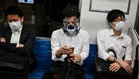 A man wearing a respirator and googles sits in between facemask-clad commuters in a train in Tokyo