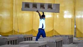 a worker carrying a cardboard bed inside the campus hall of spiritual organisation Radha Soami Satsa