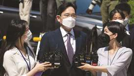 Jay Y Lee, co-vice chairman of Samsung Electronics (centre), wears a protective mask as he is surrou