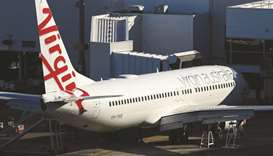 An aircraft operated by Virgin Australia Holdings stands at a gate at Sydney Airport. Bain Capital a