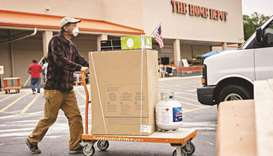 A customer wears a protective mask while pushing a cart outside a Home Depot store in Reston, Virgin