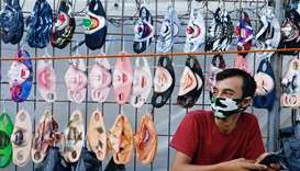 A vendor sits near a face design masks display at a traditional market, amid the coronavirus disease