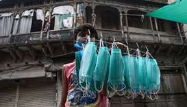 A young vendor is seen selling facemasks on a Lahore street near an area sealed by the authorities b