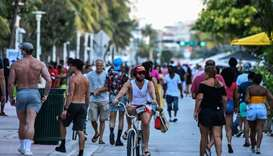 A man rides a bicycle as people walk on Ocean Drive in Miami Beach, Florida