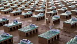 A volunteer walks past disposable beds made out of cardboard at the campus of Radha Soami Satsang Be