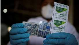 A healthcare worker holds a packet of hydroxychloroquine sulfate, azitrophar and chloroquine diphosp