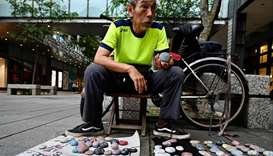 "Artist Wu Rong-bi, also as know as ""Uncle Stone"", displaying colourfully painted stones along a stre"