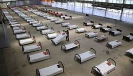 A worker arranges beds at quarantine centre set up in the Hapania International Fair Complex during