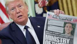 Trump holds up a front page of the New York Post as he speaks to reporters while discussing an execu