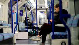 A commuter (L) wears a fdacemask on the tube in London on June 5, 2020, as lockdown measures are eas