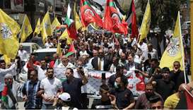 Palestinian supporters of the Fatah movement wave flags as they demonstrate in the West Bank city of