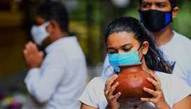 A Buddhist devotee holds a pot of water while offering prayers at the Kelaniya temple during the Pos