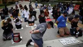 Demonstrators kneel as they take part in a protest against racial inequality in the aftermath of the