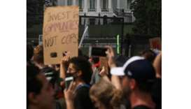 Demonstrators stand behind a fence at Lafayette Park in front of the White House during a protest ag