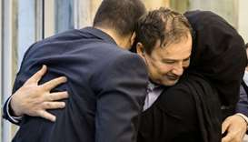 Iranian doctor Majid Taheri, who had been detained in the United States for 16 months, hugs his chil