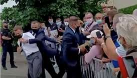 French President Emmanuel Macron is protected by a security member after getting slapped by a member