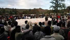 People stand in line to receive food donations, at the Tsehaye primary school, which was turned into