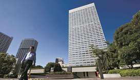 A pedestrian walks past the Toshiba Corp headquarters in Tokyo. Toshiba said it will drop two existi