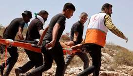 A Palestinian rescue worker and protesters carry an injured man on a stretcher during confrontations
