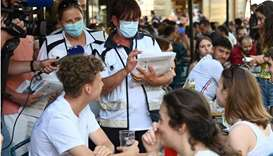 Anti-Covid mediators give information to customers on a bar terrace in Strasbourg, eastern France, o