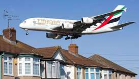 An Emirates Airbus A380 aircraft is seen above roof top