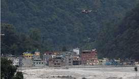 A helicopter belonging to Nepal army flies past houses hit by flash floods along the bank of Melamch