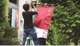 Workers attach the Tokyo 2020 Olympic Games banner on a lamp post in Tokyo, Japan, yesterday. (Reute